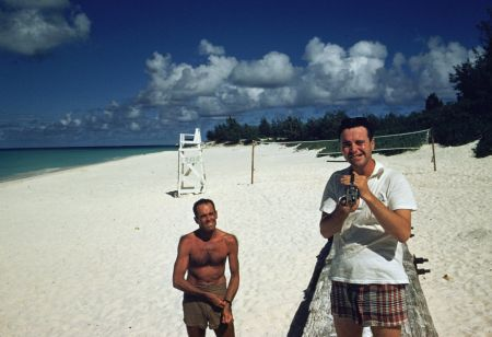jack lemmon filming slim aarons taking picture of him on beach in hawaii during filming of mister roberts. henry fonda looks on1955